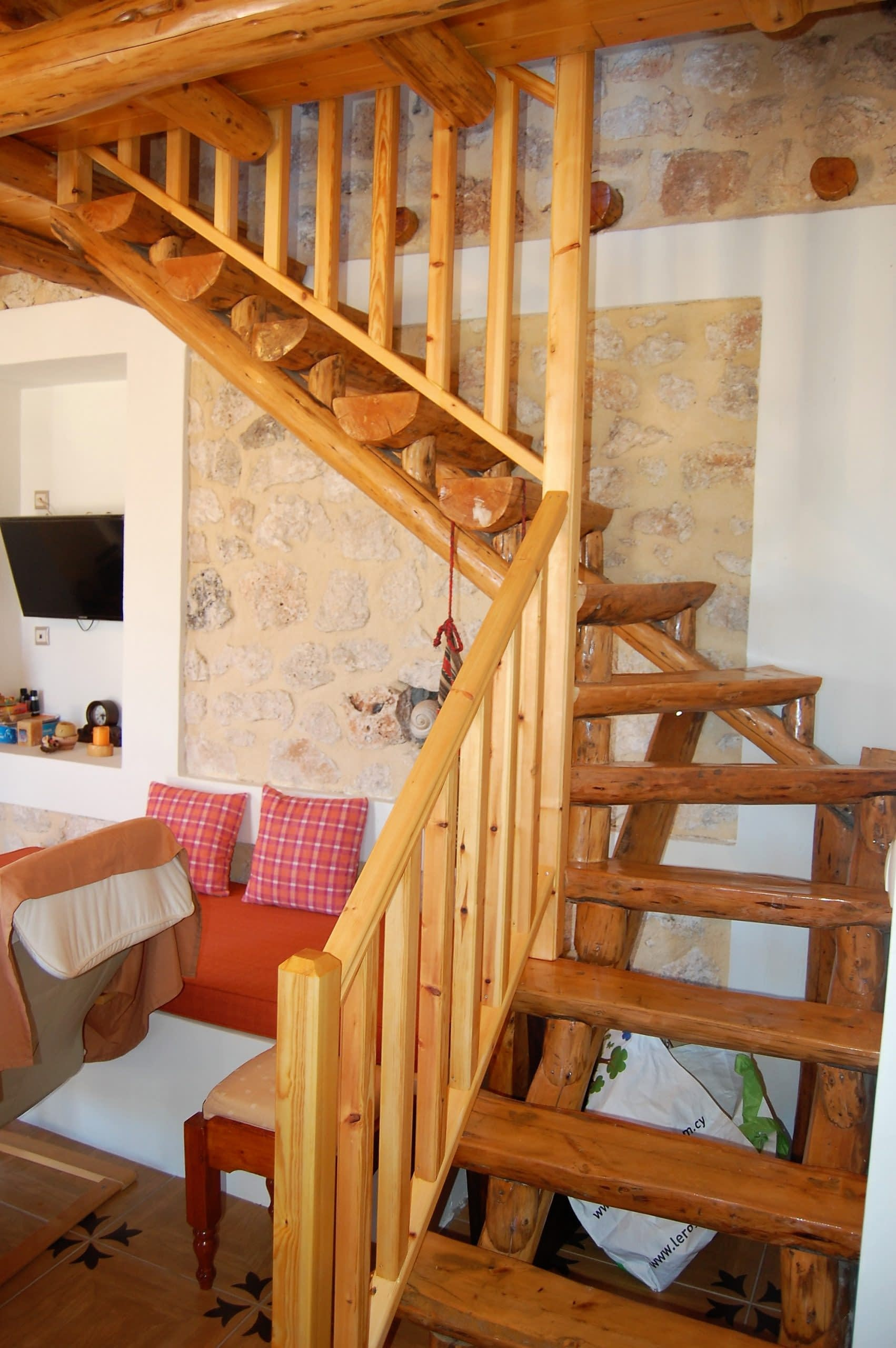 Open plan lounge with wooden staircase of stone house for rent Ithaca Greece