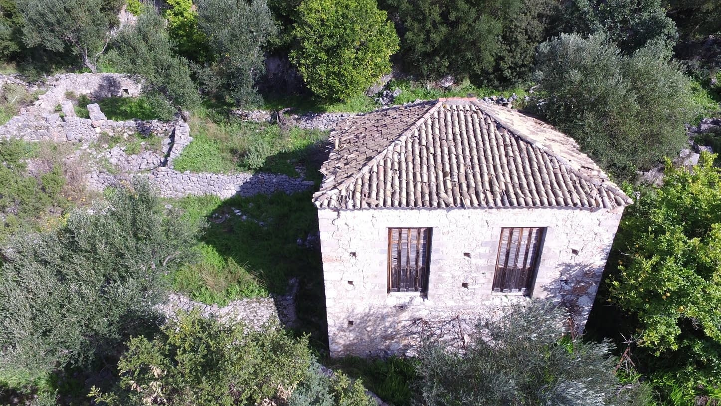 Aerial view of house with ruin for sale in Ithaca Greece Lefki