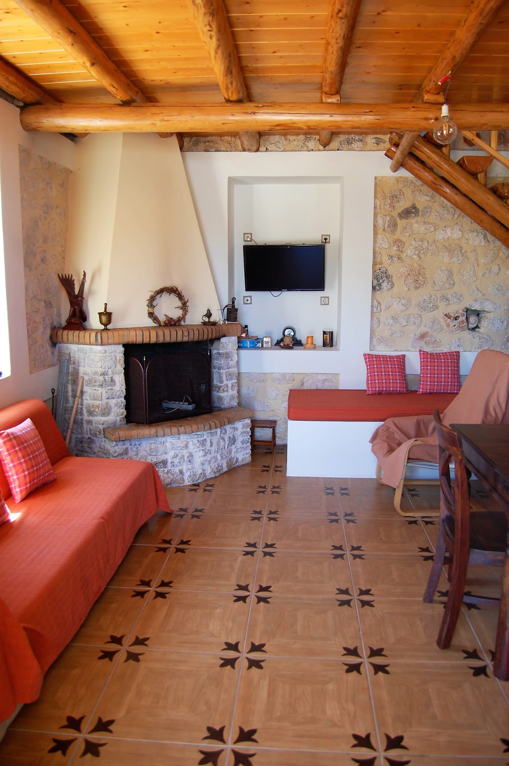Open plan lounge with fireplace of stone house for rent Ithaca Greece