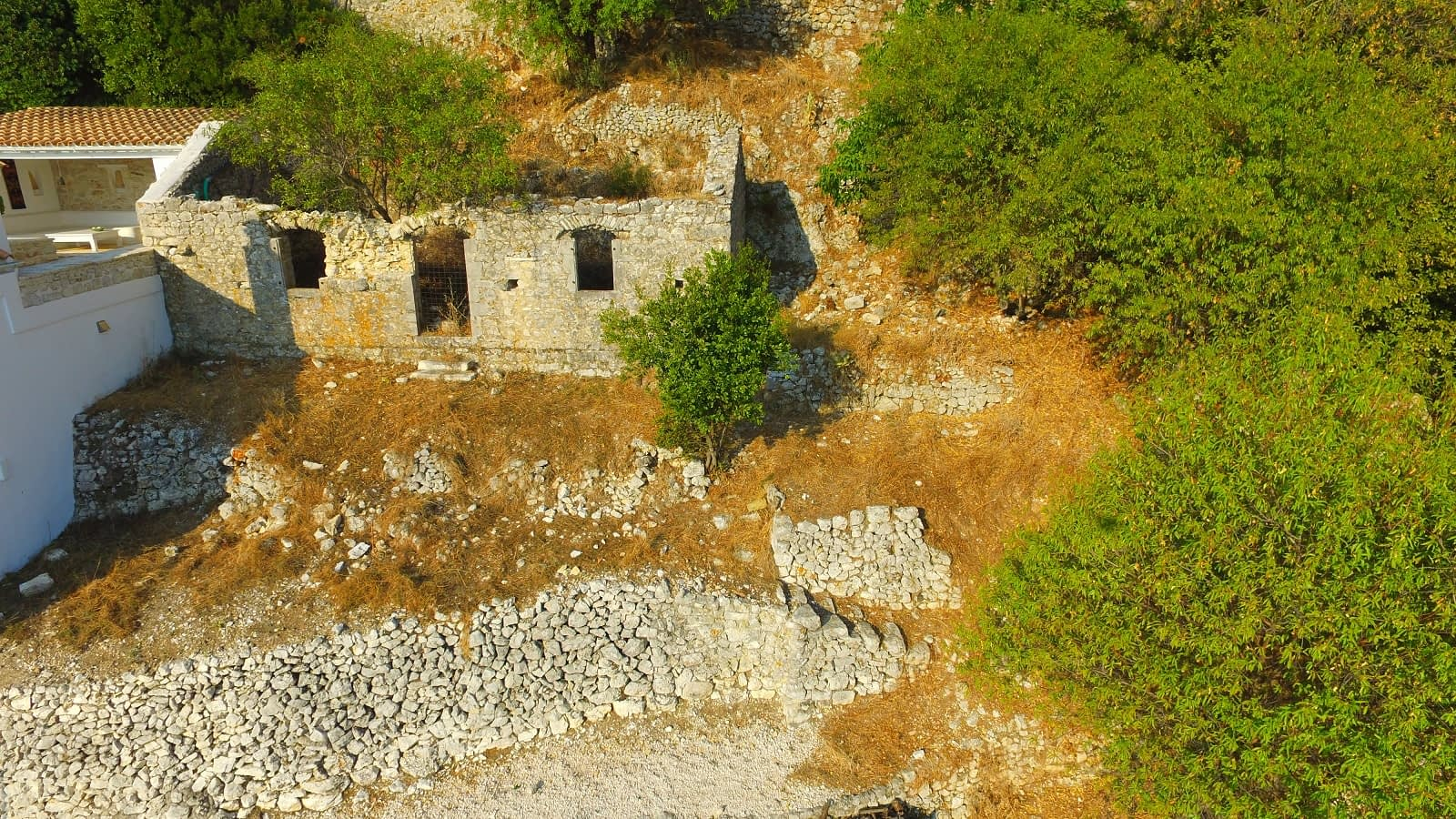 Aerial view of land with ruin for sale in Ithaca Greece Exoghi